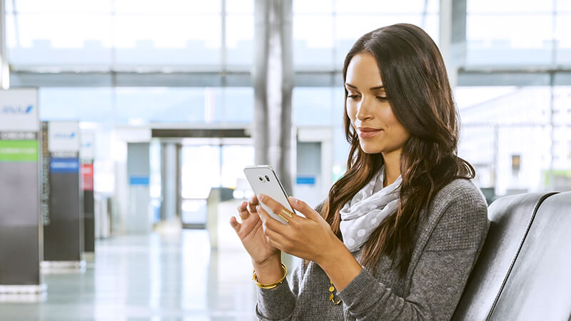 Woman at airport looking at phone