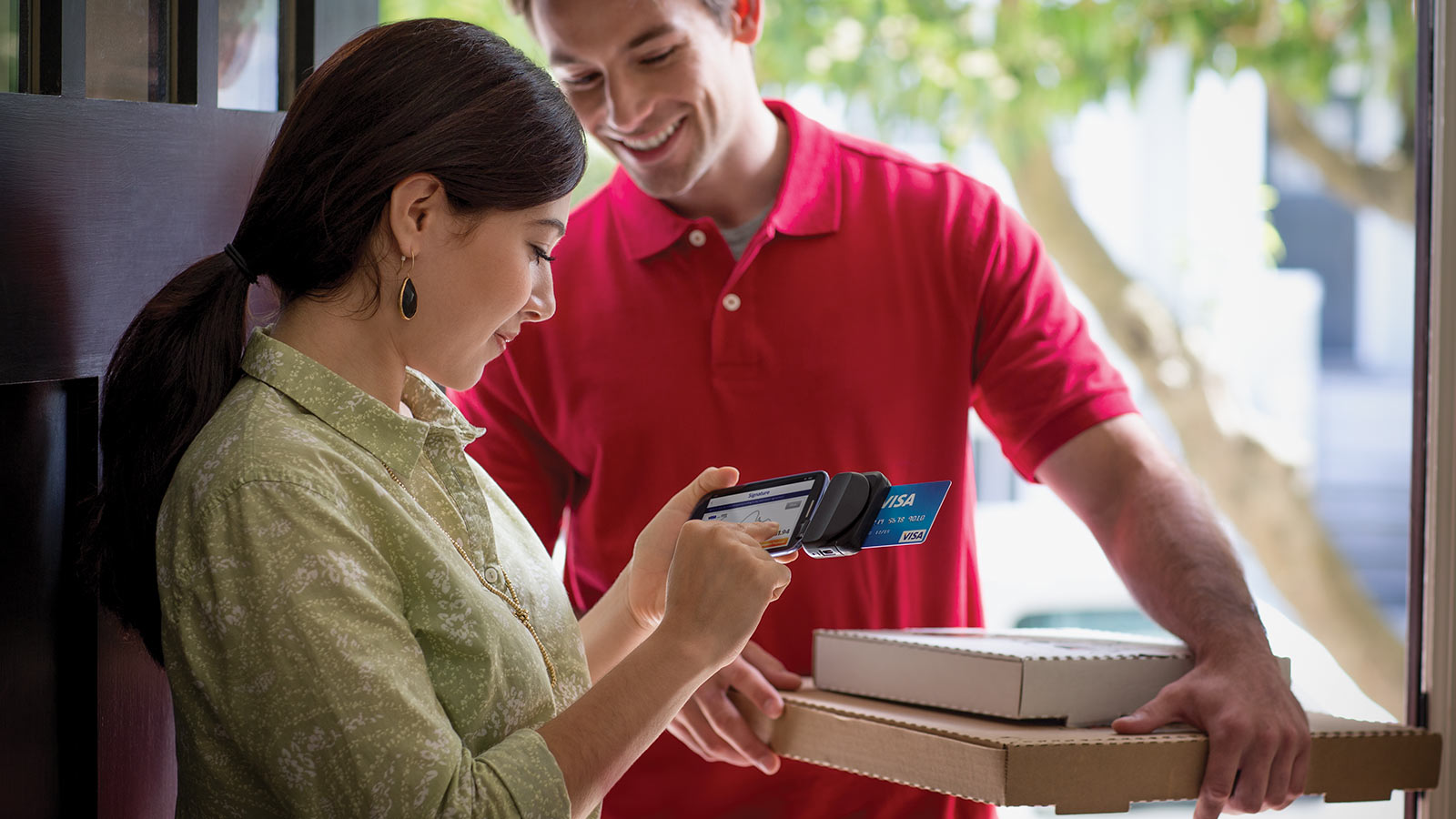 A pizza delivery person holding two pizza boxes as the customer is making a mobile payment.